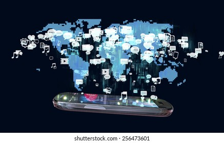 Smart phone with holographic image of world map on black background with social media messaging icons spread on it. Social media communication concept.