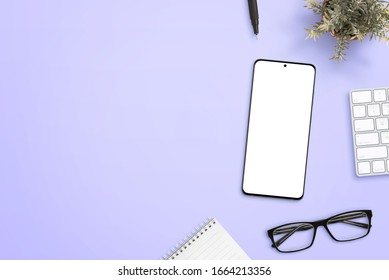 Smart phone with isolated screen for mockup on purple desk surrounded by glasses, pad, plant, keyboard and pen. Clean space beside for text