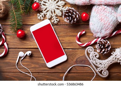 Smart phone mock up with headphones and rustic Christmas decorations for app presentation. View from above