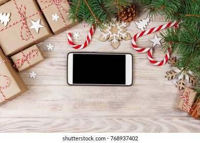 Smart phone mock up with rustic Christmas decorations for app presentation. View from above.
