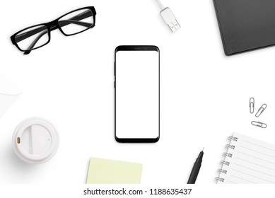 Smart phone mockup on white office desk surrounded with office supplies. Business, corporate concept. Top view.
