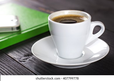 Smart phone with notebook and cup of strong coffee on wooden background. Cellphone with writing set with espresso