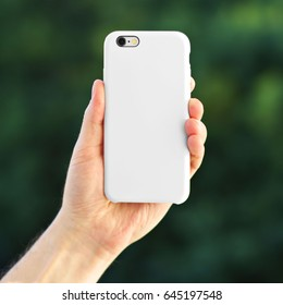 Smart phone on the blurred background of the park in a white plastic case back view. Smart phone in man's hand. Template of phone case