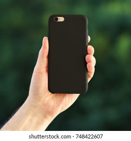 Smart phone on the blurred background of the park in a black plastic case back view. Smart phone in man's hand. Template of phone case