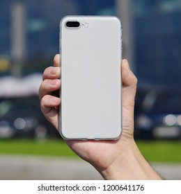 Smart phone on a blurry city background in a transparent silicone case back view. Smart phone in man's hand. Template of phone case, iPhone 8 plus case mock up