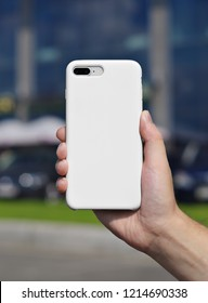 Smart phone on a blurry city background. in a white plastic case back view. Smart phone in man's hand. Template of phone case