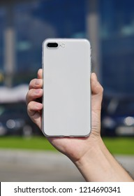 Smart phone on a blurry city background in a transparent silicone case back view. Smart phone in man's hand. Template of phone case