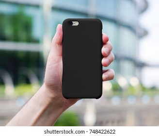 Smart phone on a blurry city background in a black plastic case back view. Smart phone in man's hand. Template of phone case