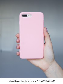 Smart phone on a gray background in a pink plastic case back view. Smartphone in a woman's hand. Template of phone case