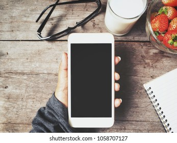Smart phone on hand with blank notepad and breakfast at desk table