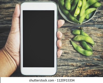 Smart phone on hand and green peas bean