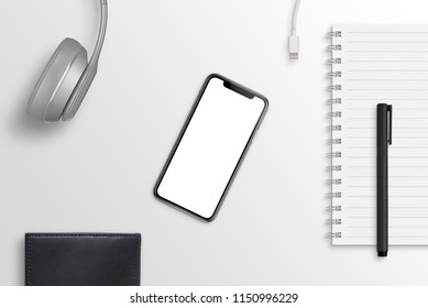 Smart phone on office desk surrounded with headphones, pad, pencil, charger, wallet. Hero header scene. Isolated screen for mockup, app design presentation.