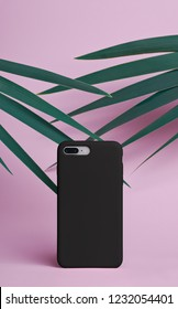 Smart phone on a pink background of palm leaves in a black plastic case back view. Template of phone case
