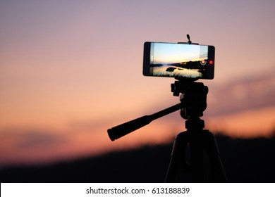 smart phone on tripod nuture view on screen at sunset