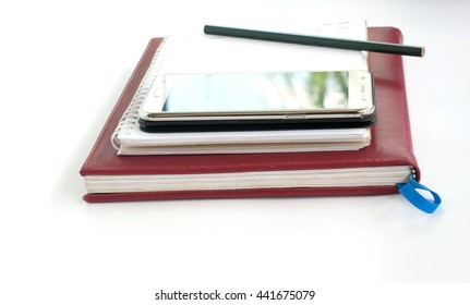 Smart phone and pencil on notebook and white background,concept for business or education.(Soft focus.)
