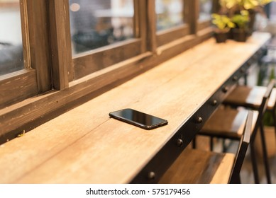 smart phone place on wooden table in coffee shop, Concept : Forget / lost, Selective focus