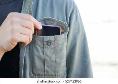 Smart phone in shirt pocket of a asian adventure man, Technology Smartphone background concept