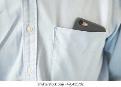 Smart phone in shirt pocket of a business man, Technology Background Concept