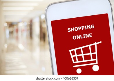 Smart phone with shopping on line on screen over blur store background, omnichannel, business and technology concept