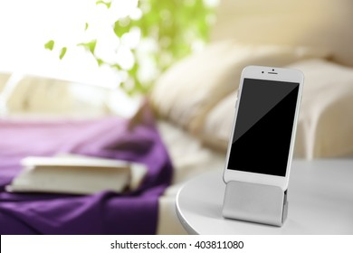 Smart phone with stand on a bedside table in a room