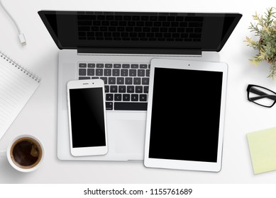 Smart phone and tablet mockup on laptop keyboard. Office desk concept. Top view.