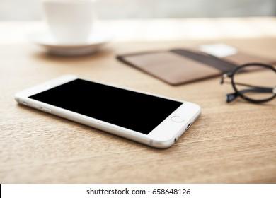 Ein Smartphone mit Portemonnaie, Brille, Kaffee, Notiz auf dem Holzschreibtisch.