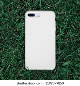 Smart phone in a white plastic case back view lies on a background of green grass. Close-up. Template of iPhone 8 plus case. Phone case mock up.