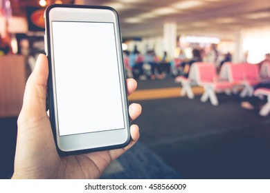 Smart phone with white screen in hand on blurred Seat airport  background