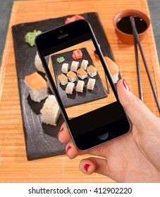 smart phone in women hand to take a photo of sushi rolls