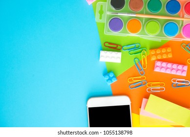smart phone,plastic toy block,clipper,water color palete,pin,on colorful background.flat lay, top view. Back to school concept