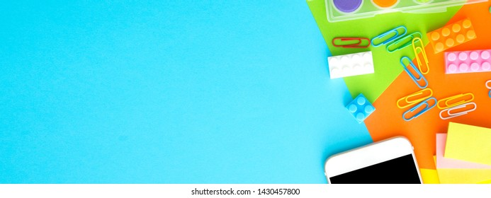 smart phone,plastic toy block,clipper,water color palete,pin,on blue background.flat lay, top view with banner ratio