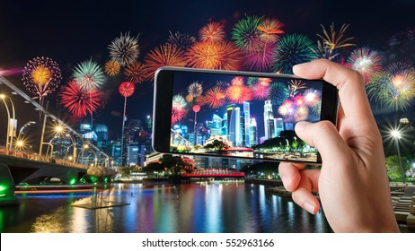 Smart phones Record Video Colorful Fireworks and Building Cityscape Skyscrapers at Night Festival, Singapore