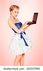 Smart pin-up girl posing over pink background with a laptop.