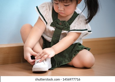 A smart precious sweet little asian 2 years old girl determine to put on her shoes by herself developing fine motor skills, brain and learn care of self in Montessori method. Child deveopment concept.