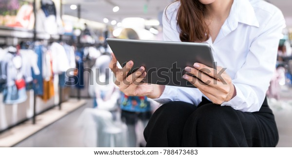 Smart retail internet of things , chatbot , online shopping technology trend concept. Female worker using tablet and blur retail shop background.