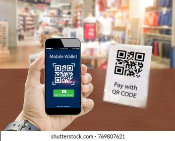 Smart retail mobile wallet payment with qr code scan concept.Hands holding mobile phone on blurred clothing store as background
