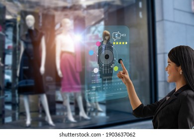smart retail, shopping online technology concept, woman try to use smart display with virtual or augmented reality in the shop or retail to choose select ,buy cloths and give a rating of products