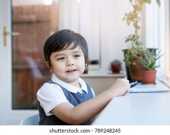 Smart school boy sitting on chair and holding magnifying glass with smiling face, Home-school Studying or Learning at home concept