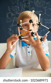 Smart school child holding plastic molecular model