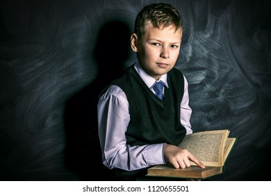 Smart schoolboy in elegant suit and spectacles standing with his book by a blackboard. Educational concept. Copy space.