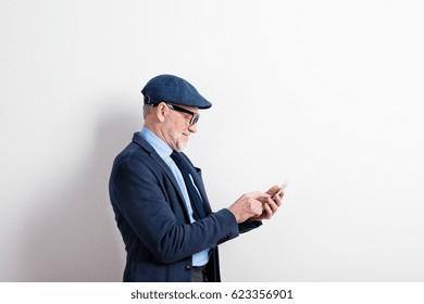 Smart senior man in suit, eyeglasses and cap, holding smartphone