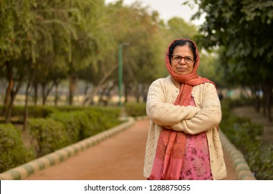 Smart senior north Indian woman standing, posing for the camera with hands crossed in a park wearing cardigan and salwar kameez in winters in Delhi, India