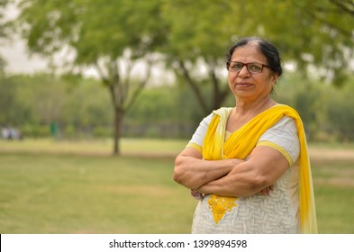 Smart senior north Indian woman standing, posing for the camera with hands crossed in a park wearing yellow salwar kameez in summers in Delhi, India