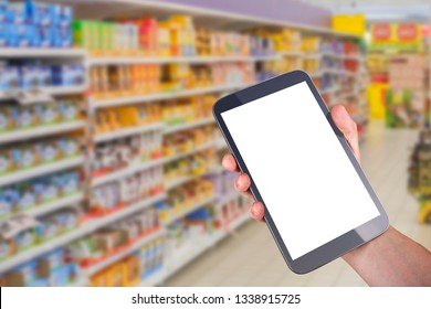 smart shopping concept tablet in hand in front of goods shelves in mall grocery. blank white screen mockup for your own creativity.
