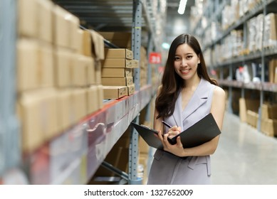Smart smiling Asian woman working in store warehouse. She is standing and holding document folder and writing some note. She is feeling happy to work. Smart working girl concept.