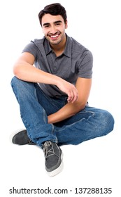 Smart smiling guy sitting on the floor, isolated over white.