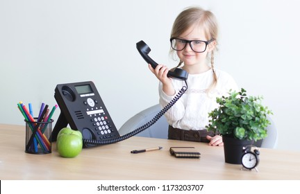 Smart, smilling little girl talking on the phone, taking notes at the office. Communication in business concept.