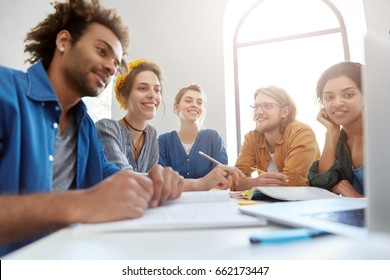 Smart students from different countries having rest while sitting at their work place looking at screen of laptop watching video relaxing after work with books. Creative workers watching presentation