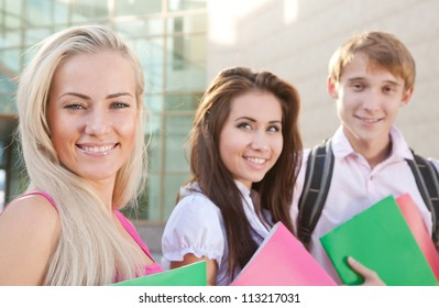 Smart students hold the books near college