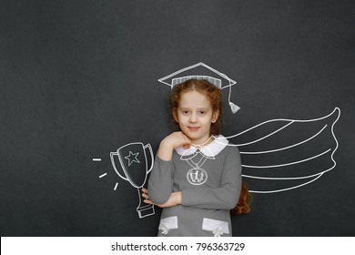 Smart superhero child with Trophy Cup near  chalkboard in classroom. Education, winner, championship, Success, creative and imagination concept.